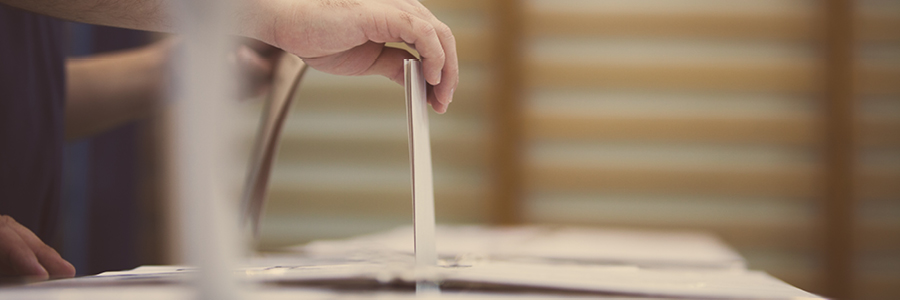 Image of a ballot being inserted into the voting box
